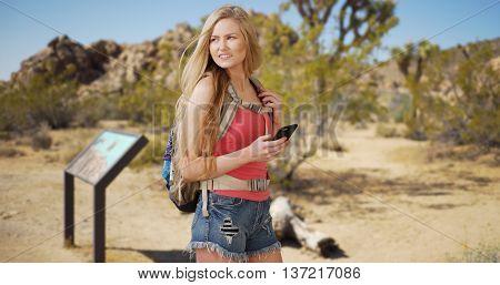 Beautiful Woman Navigating Through Joshua Tree National Park Using Mobile Device