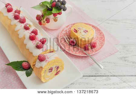 Sponge roll with with cream and raspberries on wooden background