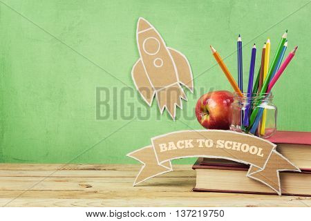 Back to school background with books pencils and cardboard rocket on wooden table.