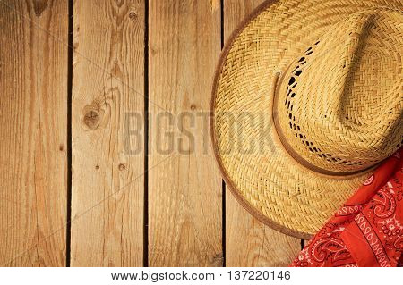 Cowboy hat on wooden vintage table with red bandanna for party invitation. View from above
