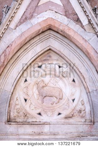 FLORENCE, ITALY - JUNE 05: Agnus Dei carrying a Christian flag, Portal of Cattedrale di Santa Maria del Fiore (Cathedral of Saint Mary of the Flower), Florence, Italy on June 05, 2015