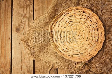 Empty wicker basket on sackcloth on wooden table background. View from above