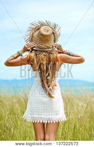 Attractive boho style woman in straw hat. Back view