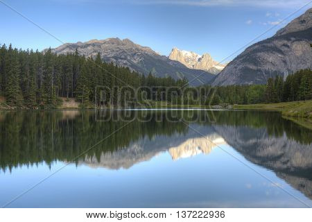 Mountains And Trees Reflecting In A Lake - Banff, Canada
