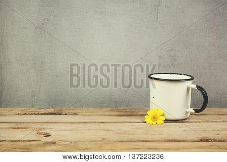 Enamel vintage coffee cup on wooden table