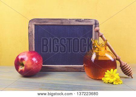 Jewish holiday Rosh Hashanah background with honey jar apple and chalkboard