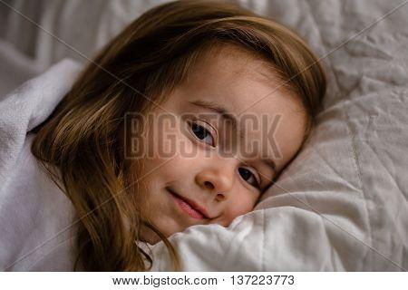 a little girl falls asleep in bed on white pillow sleep
