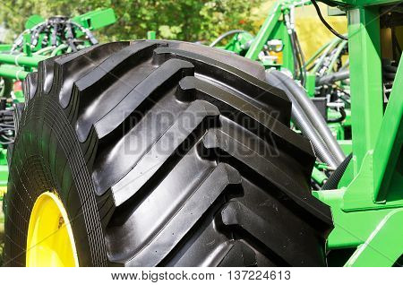 Wheeled tractor fragment background summer outdoors close up