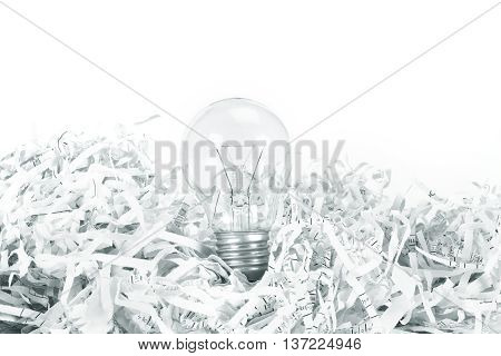 Light bulb place on shredded recycled paper on white background idea innovation concept