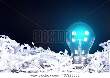 the blue Light bulb glowing place on shredded recycled paper on black background idea innovation concept