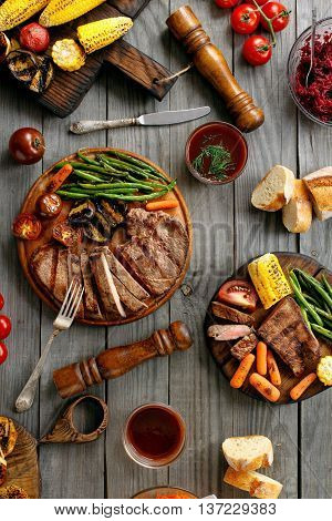 Juicy steak cooked on a grill with grilled vegetables on rustic wooden table top view. Outdoors food concept