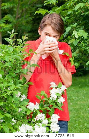 Teenage boy with hay fever blowing his nose allergic to bloom flowers in a spring garden