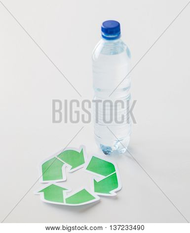 recycling, reuse, garbage disposal, environment and ecology concept - close up of plastic water bottle with green recycle symbol on table