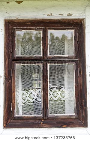 window with lace curtain of old traditional wooden polish cottage in open-air museum Ethnographic Park Kolbuszowa Poland