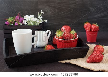 Coffee and strawberries on wooden tray over black table. White and purple flowers in a decorative wooden crate. Black background