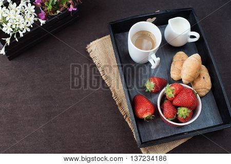 Coffee, Mini French Pastries And Strawberries On Wooden Tray Over Black Table. White And Purple Flow