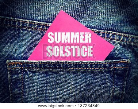 Summer Solstice word on pink sticky note in the pocket of blue denim jeans retro style