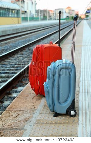 two big travel bags stands on platform near railway tracks. perspective