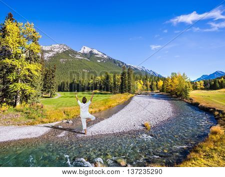 Stunned woman performing yoga in a white shirt on a rocky shoal creek. Autumn day in the Canadian Rockies, Banff Park