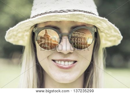 Woman in sunglasses and hat with traval images.