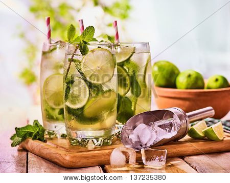 Alcohol drink. On wooden boards three glasses with alcohol drink and ice cubes. A drink number thirty six cocktail mohito and scoop ice with straw. Country life. Outdoor. Light background.