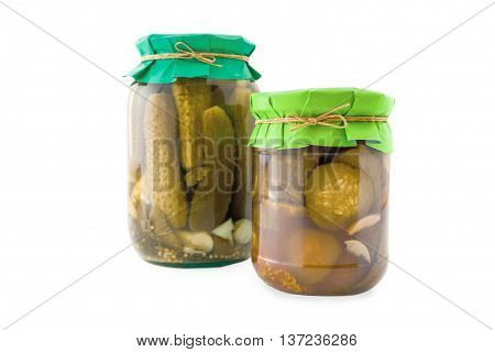 Homemade pickled cucumbers in glass jar with green paper wrapper. Homemade preserves, pickles. Jar of canned cucumbers isolated on white