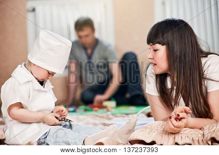 Little beautiful boy in costume of doctor at home with moter. father is on background plays wuth toys