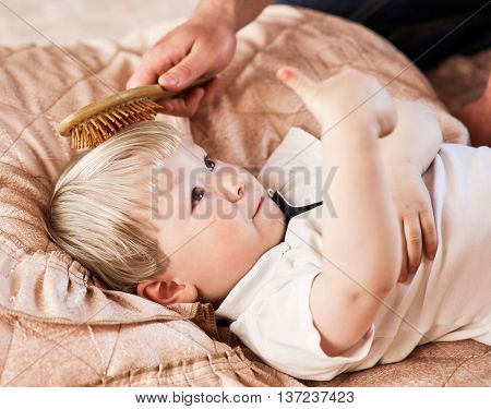 parent brushing his boy hair at home. boy shows sign ok good