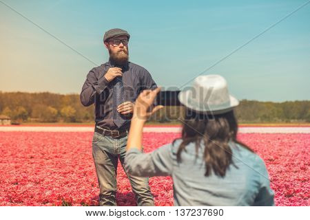 Young man with beard standing in a tulip field