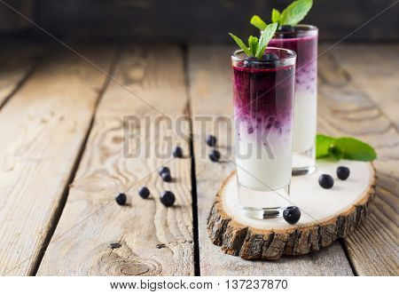 Fresh healthy blueberry smoothies in a glass with berries and mint leaves on a wooden stand.Selective focus.