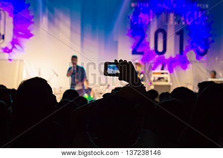 Silhouette of person take a video on mobile phone at a music festival.