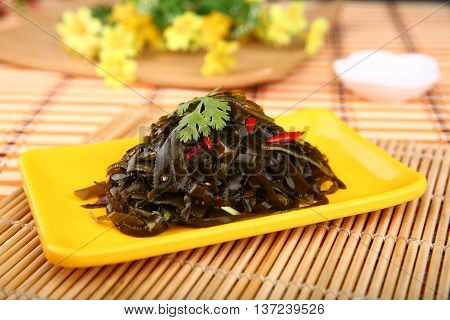 Fresh sliced seaweed on yellow plate on the table
