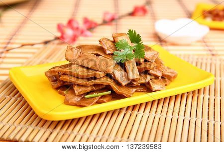 Fried sliced duck meat on yellow plate on the table in restaurant