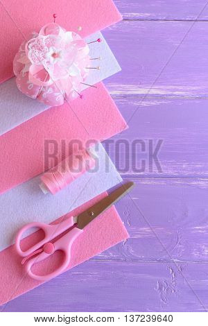 Pink and white felt sheets, pincushion, thread, needles, pins, scissors on lilac wooden background with copy space for text. DIY hand sewing set. Needlework background