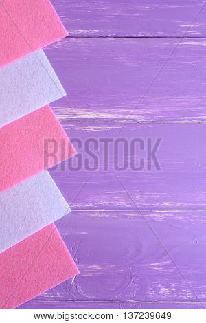 Pink and white felt sheets on lilac wooden background with copy space for text. Felt background