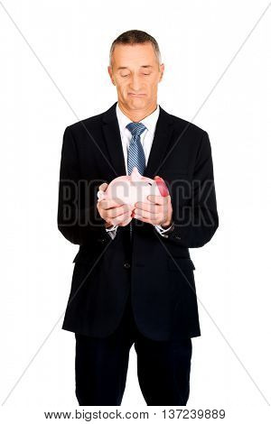Confused businessman holding piggybank