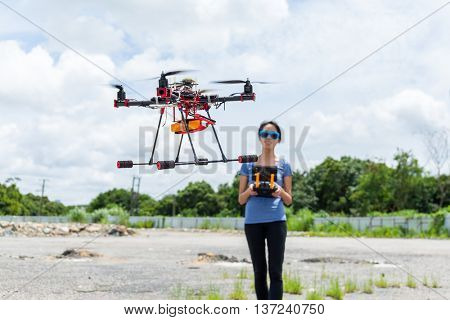 Woman controlling drone quadcopter flying