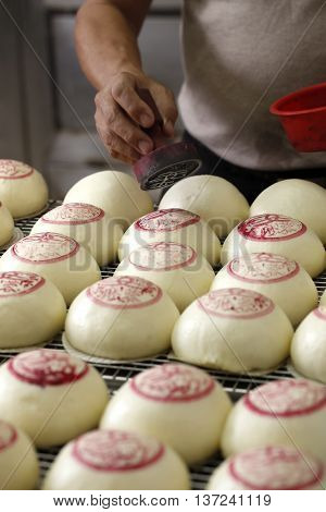 Marking red notes on chinese dumpling before baking