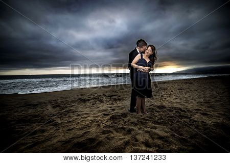 Loving engaged couple on honeymoon in a dramatic HDR beach island landscape