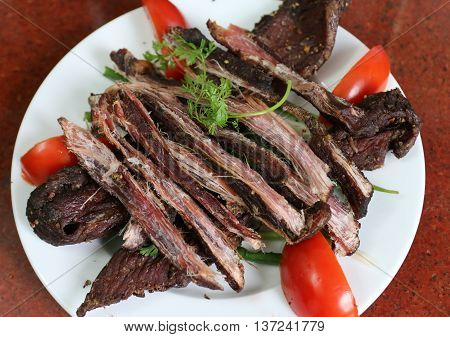 Dried buffalo meat on white dish with tomato and herbs