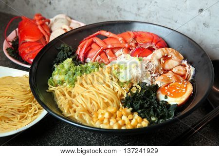 Traditional chinese bowl of wanton and vermicelli with shrimp egg corn and herbs on the table in restaurant