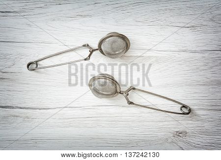 Two tea strainers on the wooden background. Kitchen equipment. Studio photo.