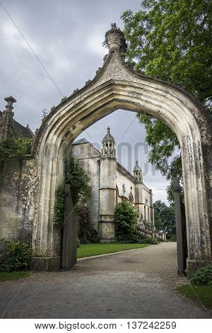 LACOCK ABBEY, LACOCK, WILTSHIRE, UK, 21 JUNE 2016 - View of the abbey through the arch