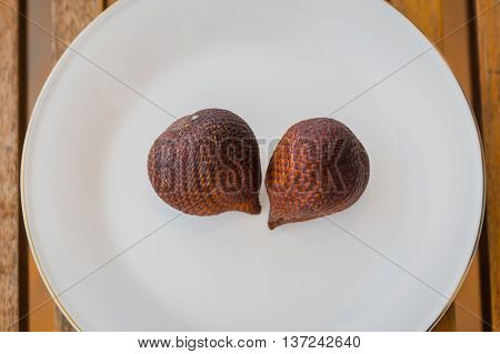 Two snake fruits are on the plate