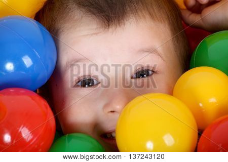 smiling boy playing in colorful balls playground