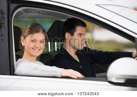young couple man and woman in silver car man in driving focus on pretty woman