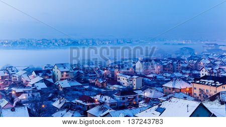 foggy winter city landscape with snow and houses
