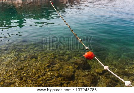 line of red buoys on the rope floating in the sea