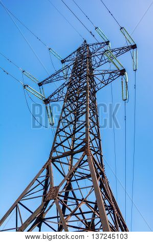 High voltage post. Electricity pylon against blue sky