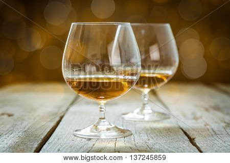 Cognac in glasses on rustic background with bokeh at background